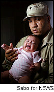 Spec. Matthew holds his deformed daughter.