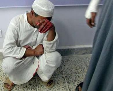 An Iraqi man, kneeling on the floor in grief.