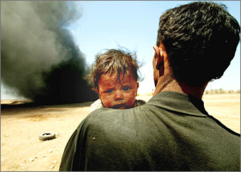 An ash-covered child hugs his father and looks away from a burning building.