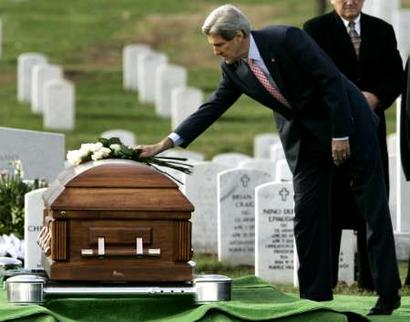 John Kerry lays flowers on the coffin of a soldier.