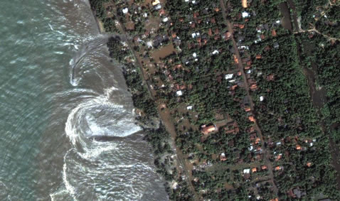 Satellite shot of tsunami sweeping in.