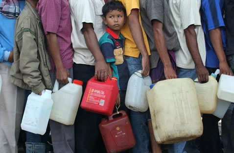 A boy waits in line for water.