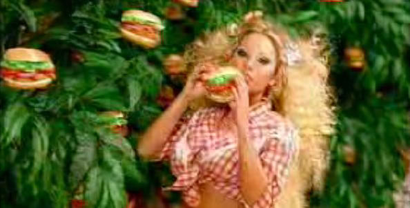 Blonde girl eating a burger with no joy.