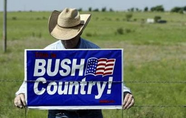 Man hangs BUSH COUNTRY sign in Crawford, Texas. (Reuters/AP/Yahoo)